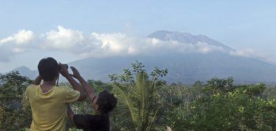 A man observes the Mount Agung with binoculars at a viewing point in Bali, Indonesia, Wednesday, Sept. 20, 2017. Officials have more than doubled the size of evacuation zone around the Mount Agung volcano o the tourist island of Bali and raised its alert level for the second time in less than a week. (AP Photo/Firdia Lisnawati)