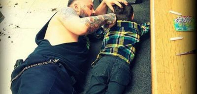 """A barber from western Quebec is drawing widespread praise for going out of his way to accommodate a young client with autism. This handout photo, posted online last week, shows Francis """"Franz"""" Jacob lying on the floor of his Rouyn-Noranda shop as he gives a young boy named Wyatt a haircut. THE CANADIAN PRESS/HO-Franz Jacob, *MANDATORY CREDIT*"""