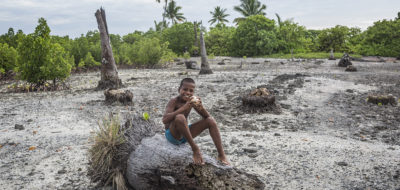 "Tekua, 10, sits on a dead coconut tree in the village of Tebunginako, Abaiang Atoll, South Tarawa, Kiribati, Saturday 30 January 2016. Residents of the village have been planting mangroves in the area that usually floods at high tide. Abaiang is most threatened by rising sea levels. The country's government says Tebunginako is a ""barometer for what Kiribati can expect in the future"". Since the 1970s residents have seen sea levels rise and erosion has meant that a major part of the village has had to be abandoned. UNICEF runs several programmes on Abaiang, including KIRIWATSAN, a project to increase access to safe and sustainable water and sanitation and reduce water, sanitation and hygiene (WASH)-related diseases.Pacific island countries face critical climate change challenges, according to a June 2016 report by the World Health Organization, UNICEF and other agencies entitled ""Sanitation, drinking-water and health in Pacific island countries: 2015 update and future outlook"". Kiribati is particularly vulnerable to the impacts of climate variability and change, and subject to a relatively high frequency of hazards such as cyclones, floods and droughts. At 47 deaths per 1000 live births, Kiribati has one of the highest rates of under-5 mortality in the Pacific region. This is mainly due to diarrhoeal disease, caused by inadequate access to safe drinking-water and sanitation. In densely-populated South Tarawa, very shallow water lenses are highly vulnerable to contamination. The lack of sanitation in Kiribati has been described as being at ""crisis levels"" in terms of the risk it poses to public health and scarce water resources. UNICEF works with the government and nongovernmental organizations to support the construction of water and sanitation facilities for communities, schools, and health centres in Kiribati. UNICEF programmes also assist the government and communities to build resilience to hazards and climate variability through better information, im"