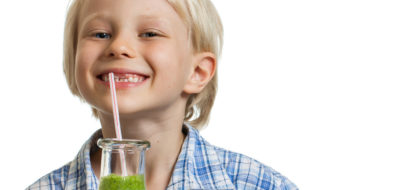 A smiling cute young boy drinking a green smoothie from a straw. Isolated on white.