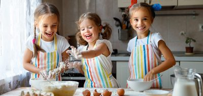 happy sisters children girls bake cookies, knead dough, play with flour and laugh