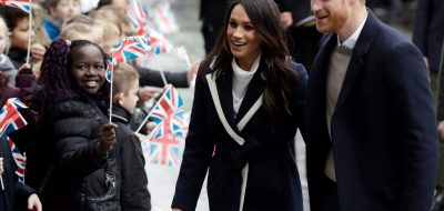 FILE - In this Thursday, March 8, 2018 file photo, Britain's Prince Harry and his fiance Meghan Markle are greeted by flag waving school children as they arrive to take part in an event for young women as part of International Women's Day in Birmingham, central England. Kensington Palace says the California-born Markle intends to take U.K. citizenship after she marries Harry on May 19 at Windsor Castle. (AP Photo/Matt Dunham, File)