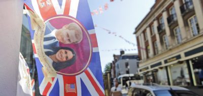 A flag with the image of Prince Harry and Meghan Markle is displayed outside a shop in Windsor, Tuesday, May 15, 2018. Preparations are being made in the town ahead of the wedding of Britain's Prince Harry and Meghan Markle that will take place in Windsor on Saturday May 19. (AP Photo/Frank Augstein)
