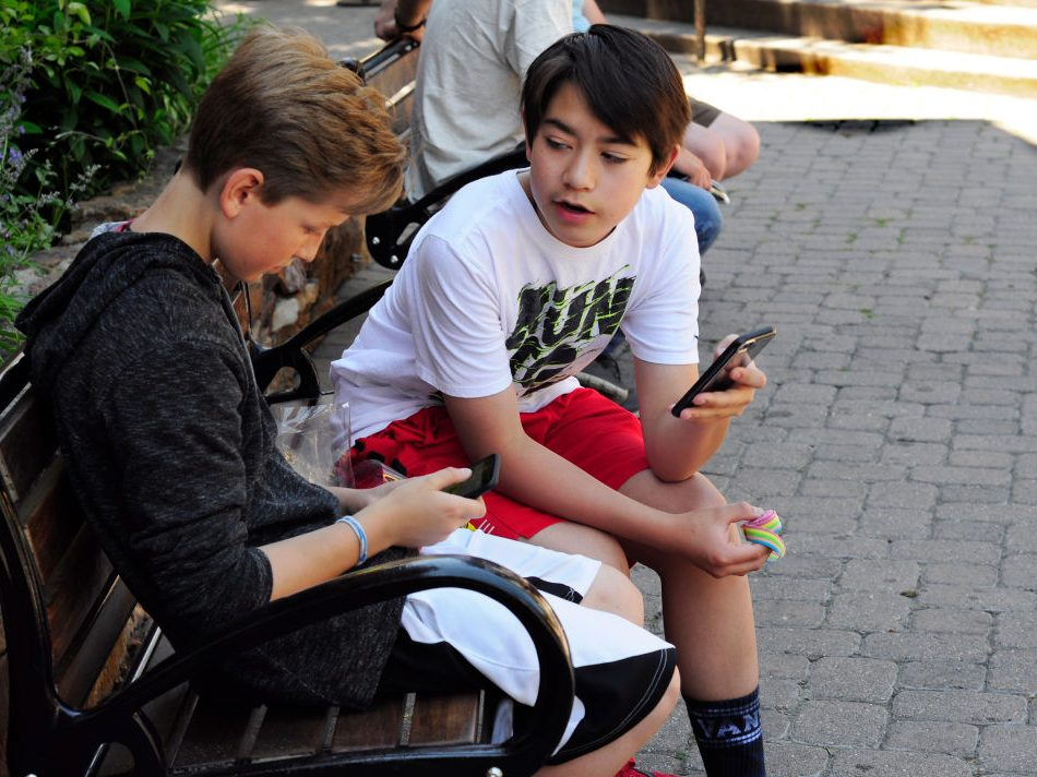 VAIL, CO - JUNE 9, 2017:  Two teenage boys use their smartphones as they sit on a bench in Vail, Colorado. (Photo by Robert Alexander/Getty Images)