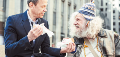 Businessman dividing his burger in two parts giving one to homeless