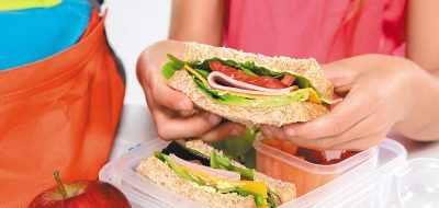 Child removing wholemeal sandwich out of lunchbox