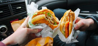 Cropped Image Of Hands Holding Hamburger In Car
